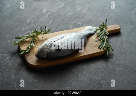one fresh raw dorada fish with rosemary, pepper and salt on a wooden board and a black table - Stock Photo