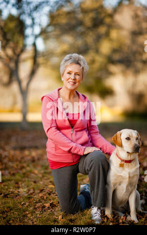 Portrait of a smiling senior woman in a park with her dog. - Stock Photo
