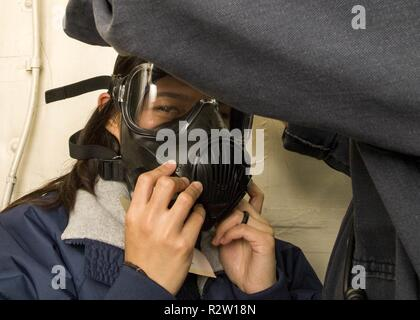 MEDITERRANEAN SEA (Nov. 6, 2018) Fire Controlman 3rd Class Amanda Bertubin gets fitted for a gas mask during a simulated chemical, biological, and radiological exercise aboard the San Antonio-class amphibious transport dock ship USS Anchorage (LPD 23) in the Mediterranean Sea, Nov. 6, 2018. Anchorage and embarked 13th Marine Expeditionary Unit are deployed to the U.S. 6th Fleet area of operations as a crisis response force in support of regional partners as well as to promote U.S. national security interests in Europe and Africa. - Stock Photo