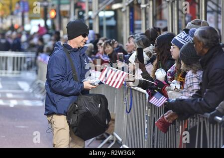 Chief Master Sgt. Thomas Daniels, 11th Wing and Joint Base Andrews command chief, passes out JBA memorabilia to Veterans Day Parade spectators in New York, Nov. 11, 2018. The Veteran's Day Parade is the nation's largest parade honoring United States Veterans, with anywhere from 25 to 40 thousand attendees and millions of television viewers. - Stock Photo