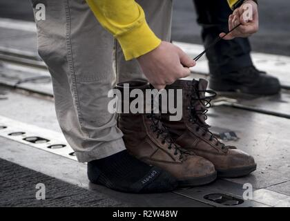 ATLANTIC OCEAN (Nov. 10, 2018) Lt. Cmdr. Ty Fritz, from Easton, Maryland, prepares to shoot his boots off the aircraft carrier USS George H.W. Bush (CVN 77). Navy catapult officers traditionally launch their boots at the end of a successful tour. GHWB is underway in the Atlantic Ocean conducting routine training exercises to maintain carrier readiness. - Stock Photo