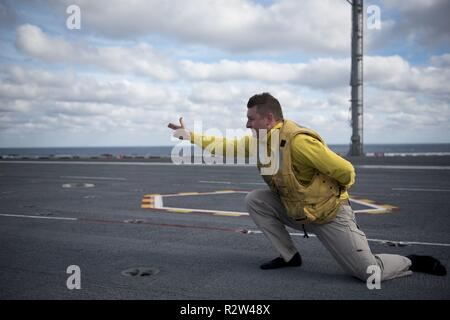 ATLANTIC OCEAN (Nov. 10, 2018) Lt. Cmdr. Ty Fritz, from Easton, Maryland, gives the signal to launch his boots from the catapult aboard the aircraft carrier USS George H.W. Bush (CVN 77). Navy catapult officers traditionally launch their boots at the end of a successful tour. GHWB is underway in the Atlantic Ocean conducting routine training exercises to maintain carrier readiness. - Stock Photo