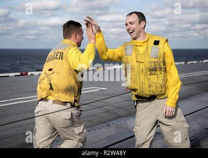 ATLANTIC OCEAN (Nov. 10, 2018) Lt. Cmdr. Ty Fritz, left, from Easton, Maryland, high-fives fellow shooters after launching his boots from the aircraft carrier USS George H.W. Bush (CVN 77). Navy catapult officers traditionally launch their boots at the end of a successful tour. GHWB is underway in the Atlantic Ocean conducting routine training exercises to maintain carrier readiness. - Stock Photo