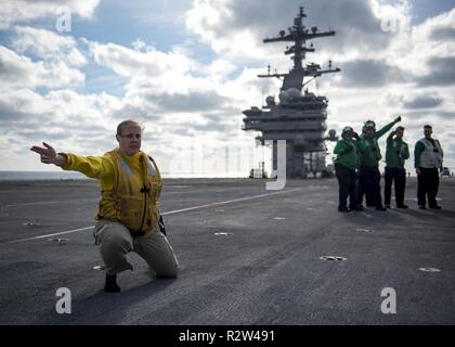 ATLANTIC OCEAN (Nov. 10, 2018) Lt. Cmdr. Bethany Harrison, from Kansas City, Missouri, gives the signal to launch her boots from the catapult aboard the aircraft carrier USS George H.W. Bush (CVN 77). Navy catapult officers traditionally launch their boots at the end of a successful tour. GHWB is underway in the Atlantic Ocean conducting routine training exercises to maintain carrier readiness. - Stock Photo