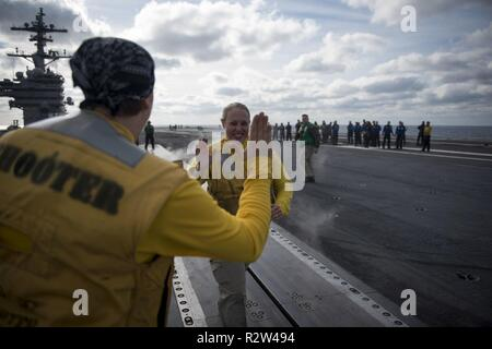 3 ATLANTIC OCEAN (Nov. 10, 2018) Lt. Cmdr. Bethany Harrison, from Kansas City, Missouri, high-fives fellow shooters after launching her boots from the aircraft carrier USS George H.W. Bush (CVN 77). Navy catapult officers traditionally launch their boots at the end of a successful tour. GHWB is underway in the Atlantic Ocean conducting routine training exercises to maintain carrier readiness. - Stock Photo