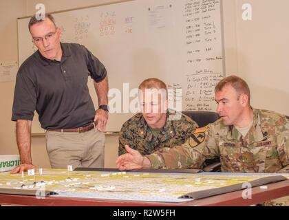 Daniel Mahoney, a Center for Army Analysis campaign planner and creator of the Tactical Wargaming Analysis Model, observes as Maj. George Gordon discusses aspects of the model with Marine Maj. Christopher Ross, Nov. 8, 2018, here. A benefit of TacWAM is that it aggregates the joint capabilities into tactical wargaming, which is a factor lacking in other Army models. - Stock Photo