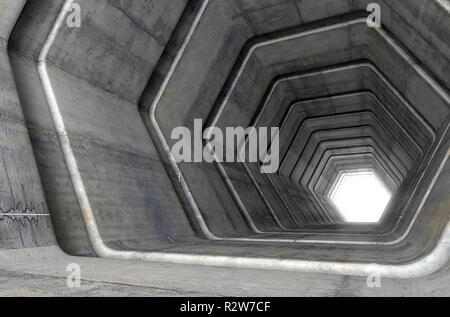 A look down a concrete tunnel made out of hexagonal geometric shapes with a light in the distance at the far end - 3D render - Stock Photo