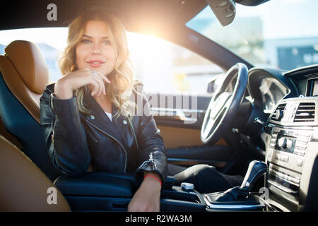 Photo of long-haired blonde sitting at wheel in car at afternoon.Sunlight effect - Stock Photo