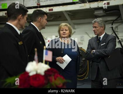 OSLO, Norway (Nov. 15, 2018) Capt. Darrell Canady, executive officer aboard the Wasp-class amphibious assault ship USS Iwo Jima (LHD 7), Rear Adm. Brad Skillman, commander, Expeditionary Strike Group 2; Erna Solberg, Prime Minister of Norway; and Kenneth J. Braithwaite, U.S. ambassador to Norway, speak in the ship's hangar bay during a dinner reception Nov. 15, 2018. Iwo Jima is currently in port in Oslo, Norway after participating in Trident Juncture 2018 which was a NATO-led exercise designed to certify NATO response forces and develop interoperability among participating NATO Allied and par - Stock Photo