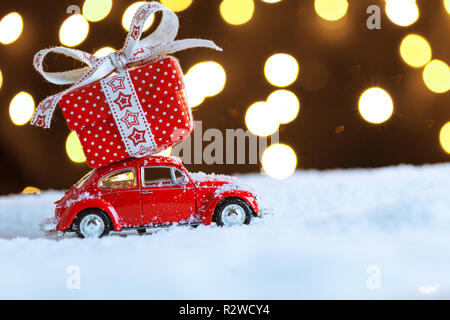 Christmas red car with gift box on snow - Stock Photo