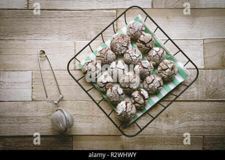 Chocolate crinkle cookies in a basket on wooden table. Top view. Landscape format. - Stock Photo