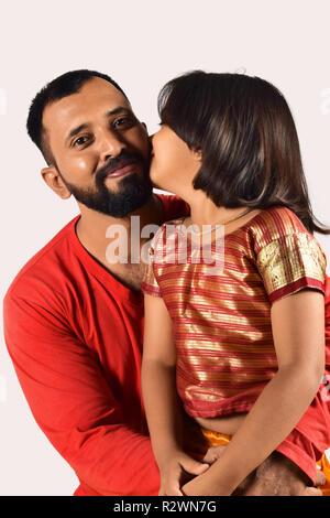Little girl kissing her father on the cheek, Pune, Maharashtra - Stock Photo