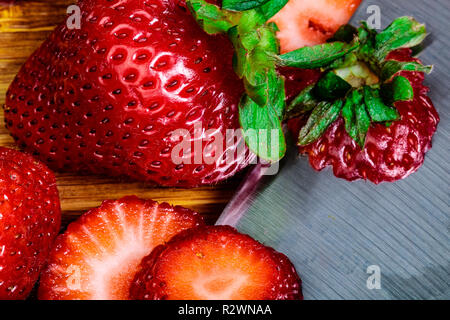 A Close up image of sliced strawberries with a whole berry.  Sliced caps are present with the knife. - Stock Photo