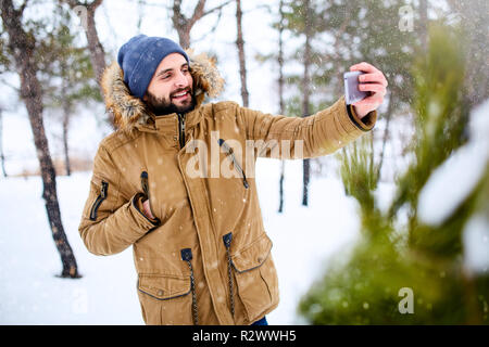 Smiling bearded man wears warm winter clothes and taking selfie photo with smartphone camera. Handsome man texting with cellphone and using apps in snowy forest. Snowfall in woods. - Stock Photo