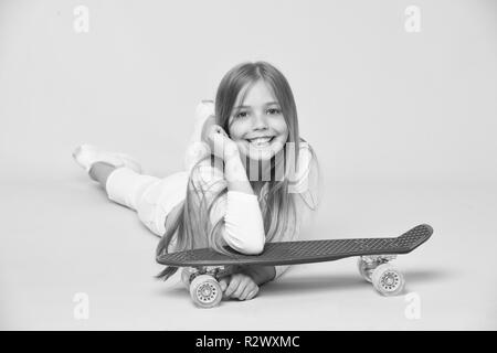 Kid in white outfit lying on floor. Girl with long blond hair isolated on pink background. Child with cute smile leaning on violet skateboard. Teenager having fun, relaxation concept. - Stock Photo