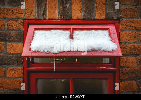 A red framed window with snow and icicles with a brick wall on the background. Landscape format. - Stock Photo