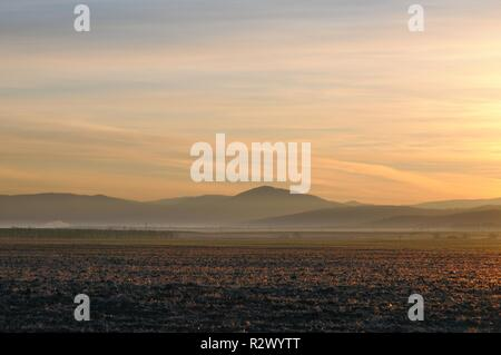 Autumn landscape with cleaned agricultural field during spectacular gold sunrise above smooth hills in Khakassia, Russia - Stock Photo