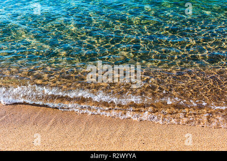 Sandy beach of warm sea. Transparent turquoise water, soft wave, sunlight reflecting on sea bottom - Stock Photo