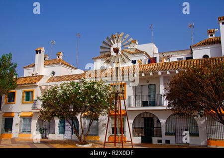 Small old windmill in front of white building, summer, Spain - Stock Photo