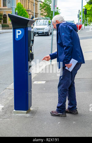 An elderly man trying to work out how to operate a newly installed solar powered parking meter in Hobart, Tasmania - Stock Photo