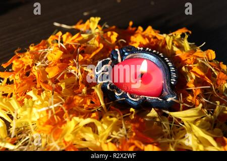 A typical view of lit diya placed on flowers for celebrating diwali and dhanteras - Stock Photo