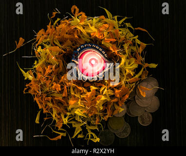 Lit diya placed on flowers for celebrating diwali and dhanteras - Stock Photo