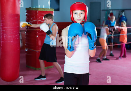 Portrait of young  serious boy boxer wearing gloves at boxing hall - Stock Photo