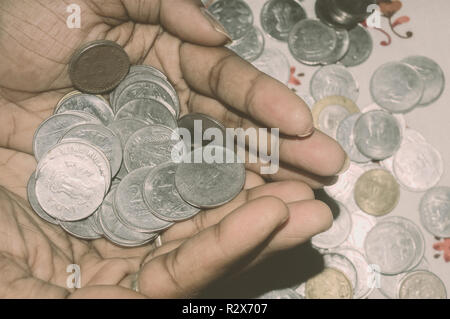 An woman hand, holding Stock pile of Hundred number 1, 10, 5 Indian rupee metal coin currency. Financial, economy, investment concept. Banking and exc - Stock Photo