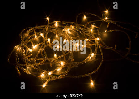 Diwali chain light, spiral shape, design to decorate street or home fireworks, dark black background shot in festival time or new years eve carnival,  - Stock Photo
