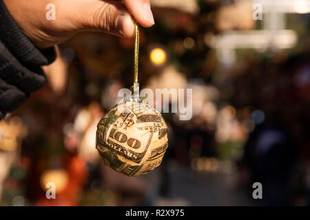 closeup of a young man holding a christmas ball wrapped on pieces of a US 100 dollar bill in a christmas market - Stock Photo