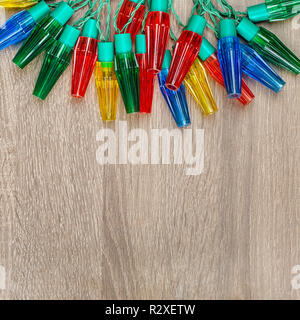 Christmas colorful lights on brown wooden background - Stock Photo