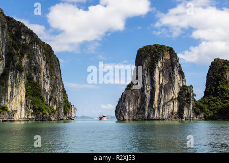 A Tourists junk boat sails between steep sided limestone rock islands in Halong Bay in South China Sea. Ha Long, Quảng Ninh, Vietnam, Asia - Stock Photo