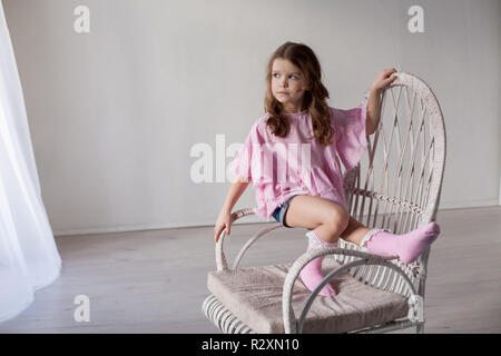 beautiful fashionable little girl sits in a Chair - Stock Photo