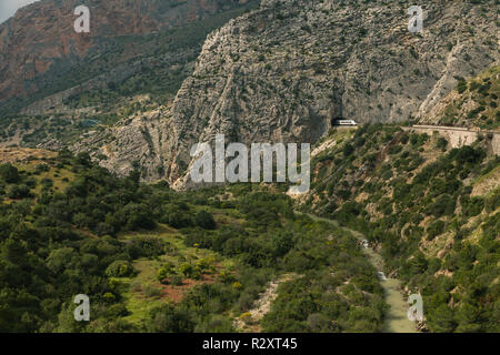 Views of a large valley with a river bellow in Ardales, Andalusia, surrounded by mountains and a train that goes through the mountain tunnel. - Stock Photo