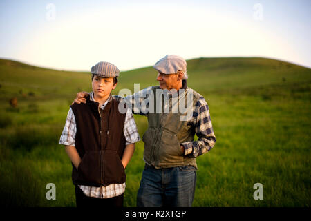 Teenage boy and his grandfather having a conversation whilst walking together through a grassy field on a farm. - Stock Photo