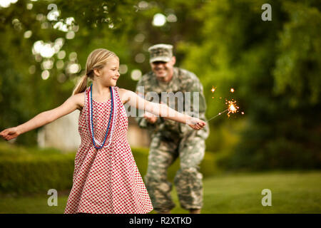 Young girl dancing with sparklers in the back yard with her father. - Stock Photo
