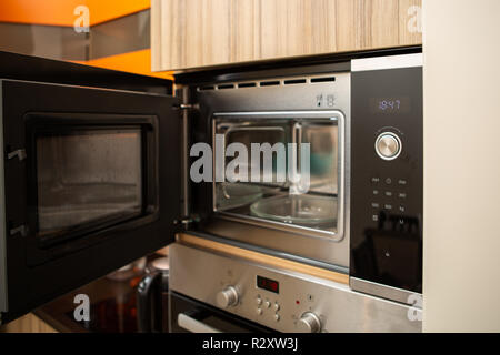 Photo of open microwave in kitchen - Stock Photo