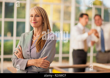 Mid adult businesswoman standing with her arms crossed. - Stock Photo