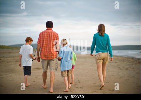 Mother and father walking with their three young children on a beach. - Stock Photo