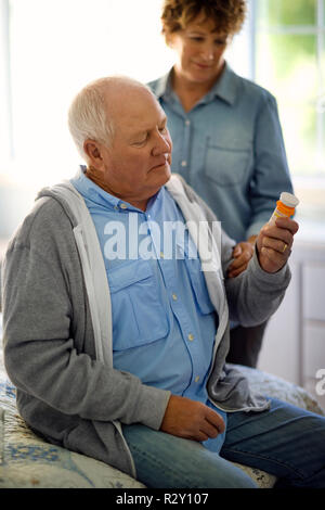 Mature man reads the instructions on the bottle before taking his medication. - Stock Photo