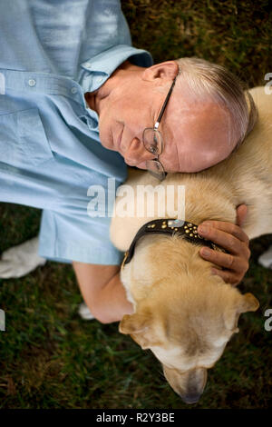 Senior man lying on the grass with his dog. - Stock Photo