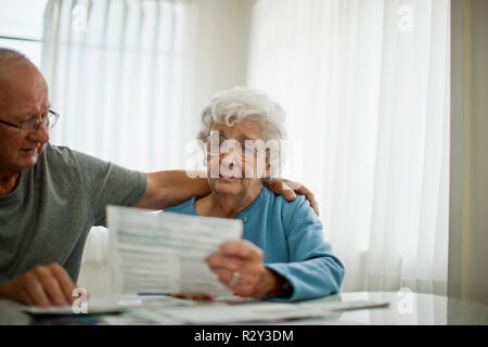 Anxious elderly couple try to comfort each other as they are worried about a bill that they have received. - Stock Photo