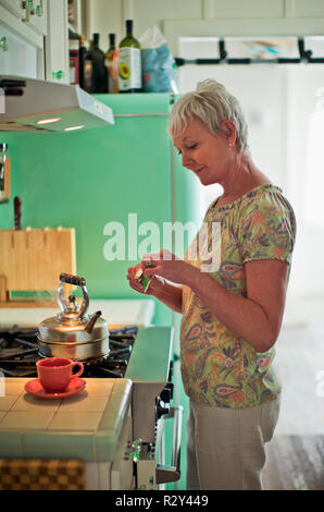 Mature woman preparing a cup of tea in her kitchen. - Stock Photo