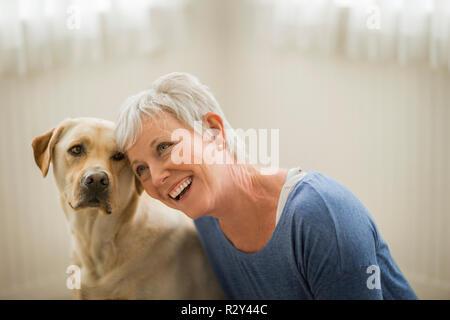Happy mature woman hugs her golden Labrador. - Stock Photo