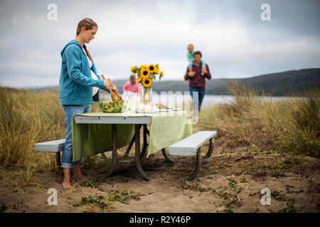Middle-aged pregnant woman prepares an outdoor lunch for her husband and children at the beach. - Stock Photo