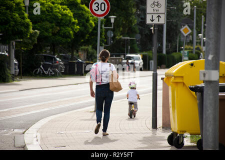 Mother german people looking children girl practice cycling on footpath at beside road in Sandhausen district and village on August 25, 2017 in Heidel - Stock Photo