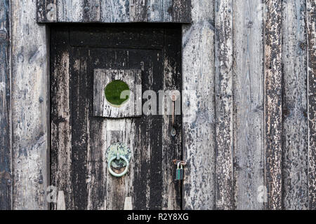 A wooden door from the Icelandic Turf House, Selfoss, Iceland. The door and the house would once have been covered in tar which is just visible. - Stock Photo