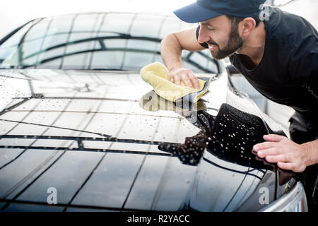 Professional washer in t-shirt and cap wiping a car hood with yellow microfiber at the open air car wash - Stock Photo