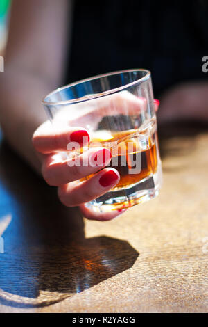 the girl is sitting in a cafe and is holding a glass of whiskey. - Stock Photo