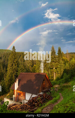Beautiful house in mountain with forest and double rainbow on background. Travel background - Stock Photo